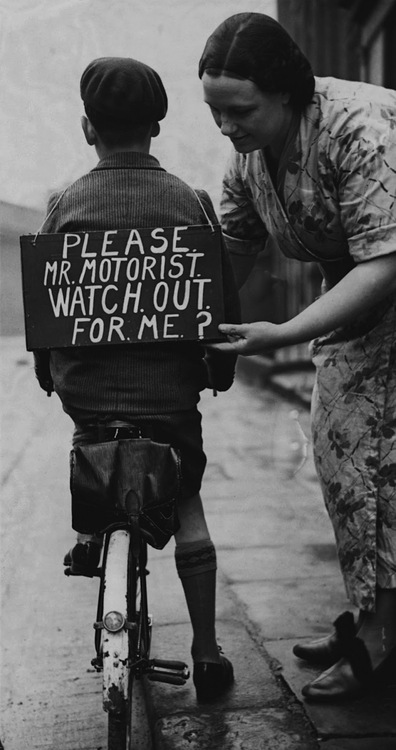 A mother fastening a notice reading onto her son's back before he sets out on a trial bicycle ride, 1937.
